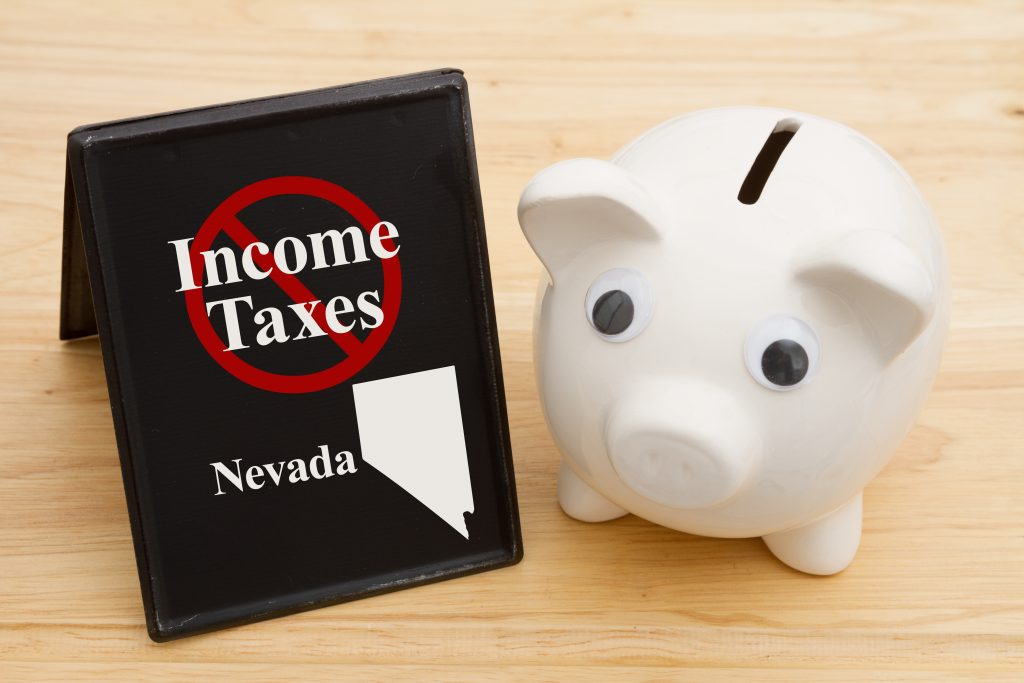 Starting a business in Nevada has the benefit of no personal or corporate income tax as demonstrated by a no income tax sign next to a white piggy bank.