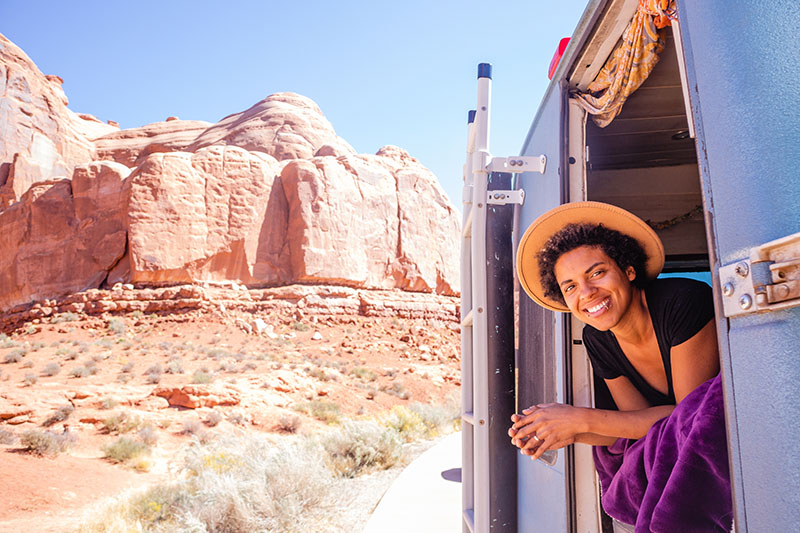 Woman hanging out the back of a camper van